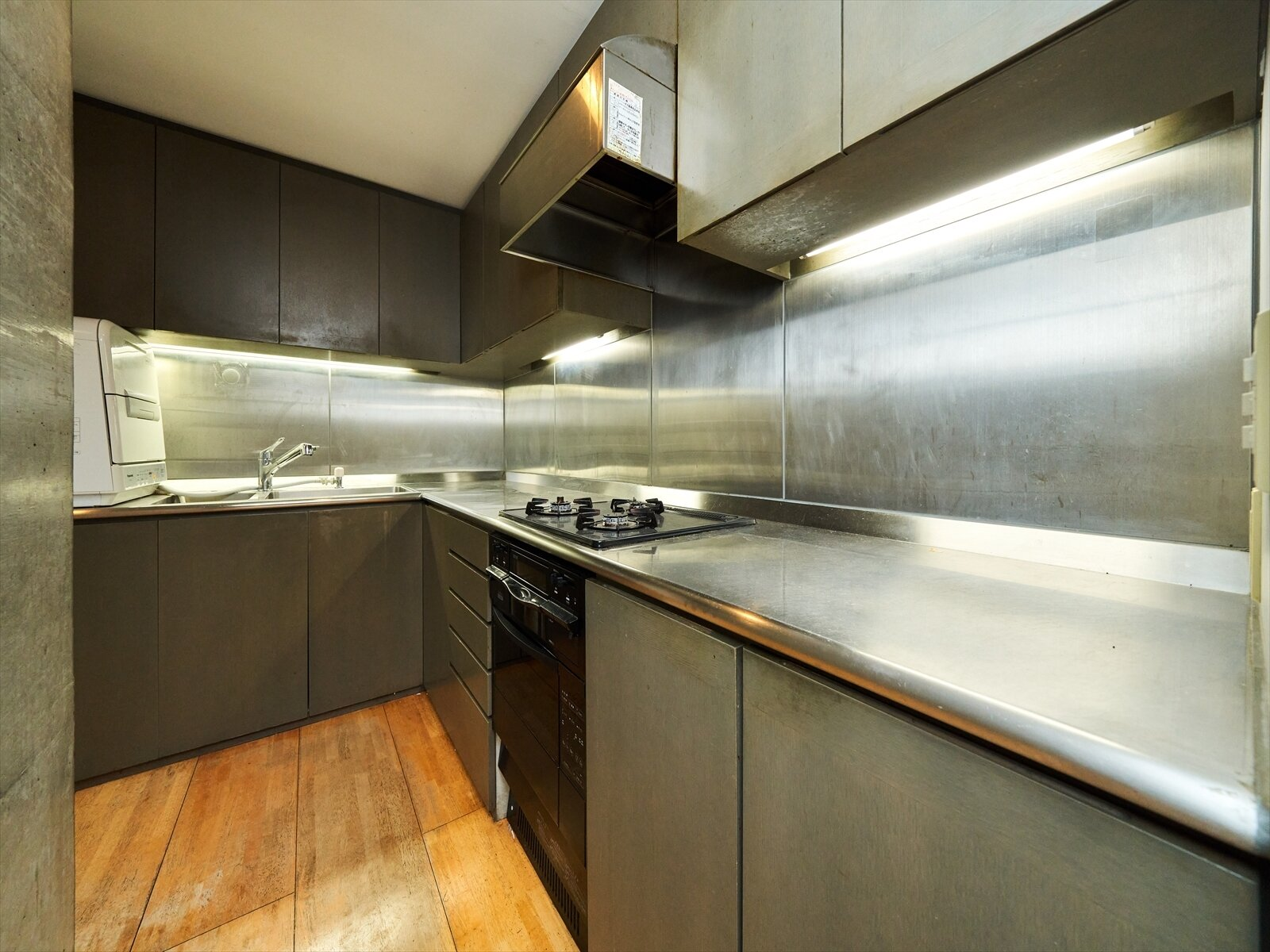 The kitchen in one unit features stainless steel countertops and wide-plank hardwood floors.  Photo 6 of 11 in Tadao Ando's Curved Concrete Ito House Asks $7M in Tokyo