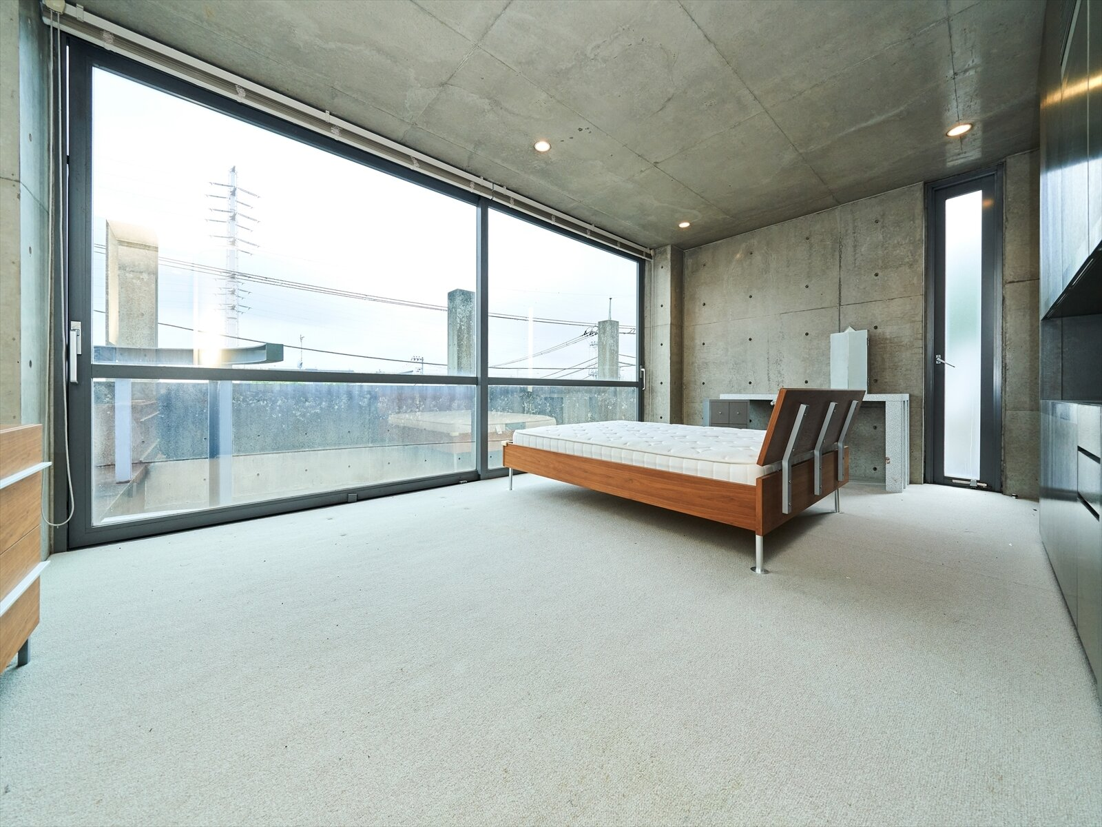 The top-floor features a large bedroom overlooking the courtyard below and rooftop patio.  Photo 7 of 11 in Tadao Ando's Curved Concrete Ito House Asks $7M in Tokyo