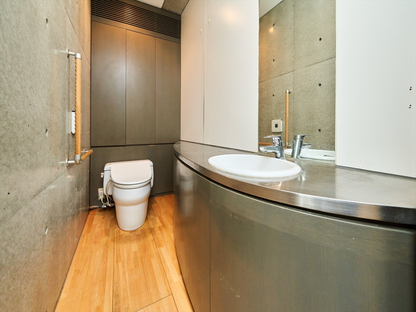 Finishes in each bathroom carry forward the exposed concrete and stainless steel found in other rooms of the apartments.  Photo 8 of 11 in Tadao Ando's Curved Concrete Ito House Asks $7M in Tokyo