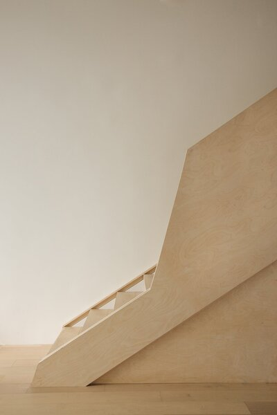 The sculptural new staircase, fronted with a faceted, Baltic birch handrail, features storage underneath that reduces clutter.