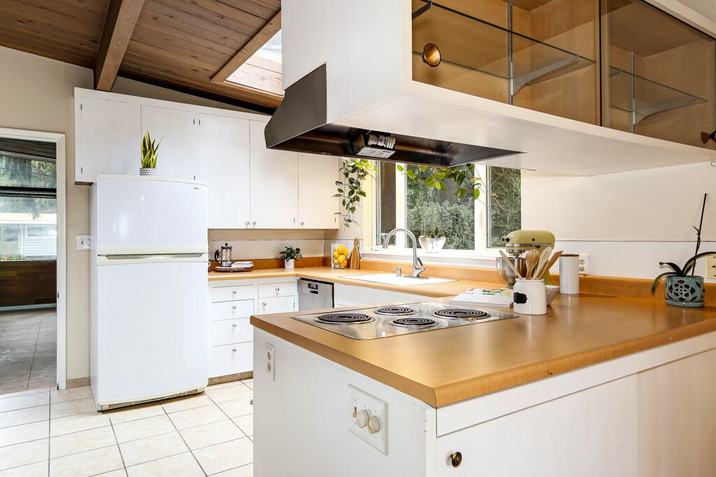 Another skylight punctuates the kitchen, allowing the open space to feel bright and airy. White-painted cabinets offer plenty of storage, while the shaded countertops add a hint of color.  Photo 8 of 13 in A Sun-Drenched Midcentury Near Seattle Seeks $750K
