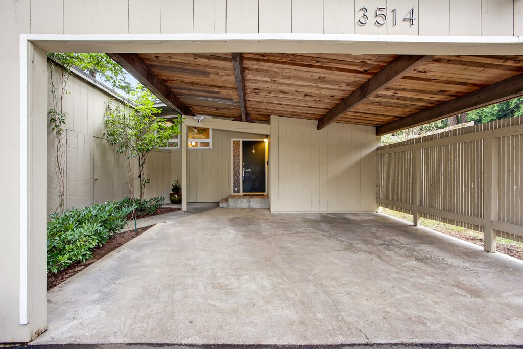 The original carport was enclosed and another one—which can comfortably accommodate two cars—was added in front of the main entry.   Photo 3 of 13 in A Sun-Drenched Midcentury Near Seattle Seeks $750K