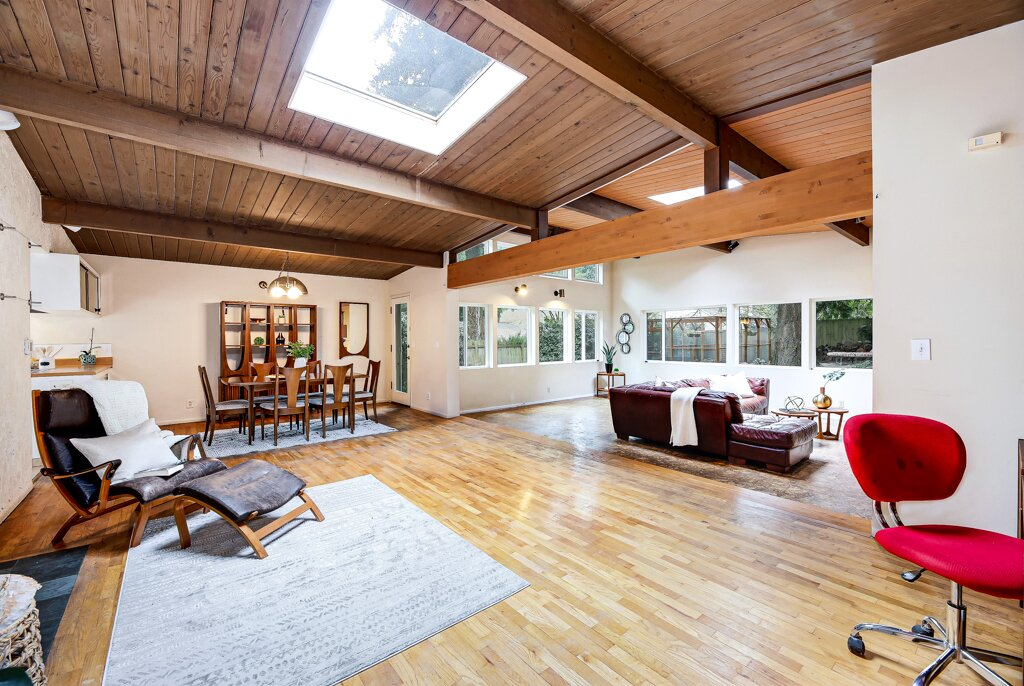 """Generous skylights in the vaulted tongue-and-groove ceilings illuminate the home. """"Even on a short, dreary Seattle winter day, we don't need to keep any lights on in the house, and it feels bright and cheerful,"""" says Kelle.  Photo 5 of 13 in A Sun-Drenched Midcentury Near Seattle Seeks $750K"""