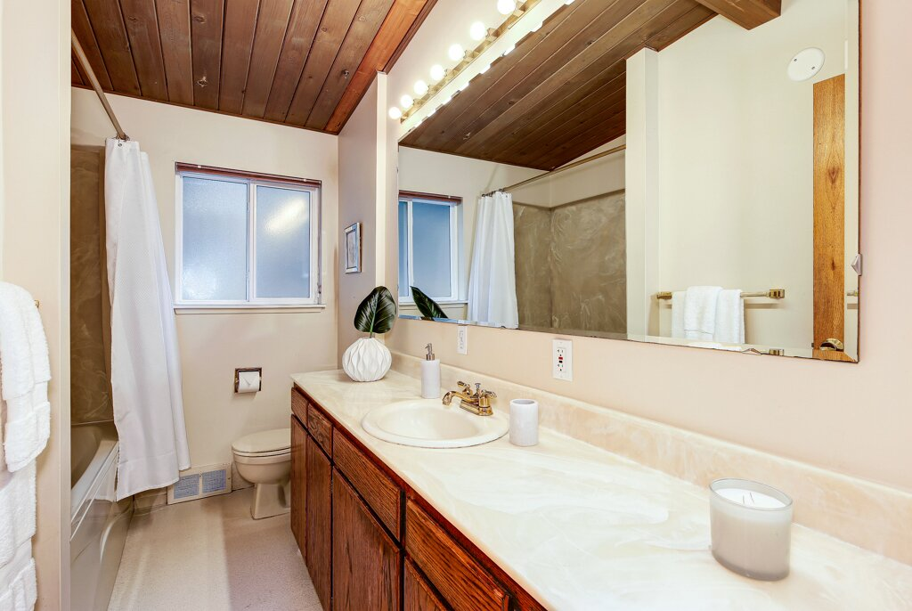A spacious, well-lit bathroom is also connected to the primary suite.  Photo 11 of 13 in A Sun-Drenched Midcentury Near Seattle Seeks $750K