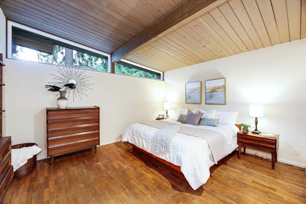 In total, the home includes three bedrooms. Here is a peek at the primary suite, which features original clerestory windows, tongue-and-groove ceilings, and hardwood floors.   Photo 10 of 13 in A Sun-Drenched Midcentury Near Seattle Seeks $750K
