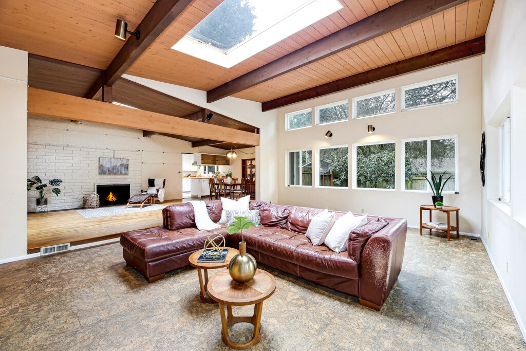 """This home benefits from a well-done, seamless living room addition which enclosed a portion of the backyard and lends a lot of light to the home with a large skylight and the clerestory windows,"" says listing agent Kristine Emerson. A brick fireplace awaits in the living area closest to the kitchen.  Photo 6 of 13 in A Sun-Drenched Midcentury Near Seattle Seeks $750K"