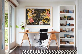 A painting by Mayumi Oda commands the wall over Ginger's desk.