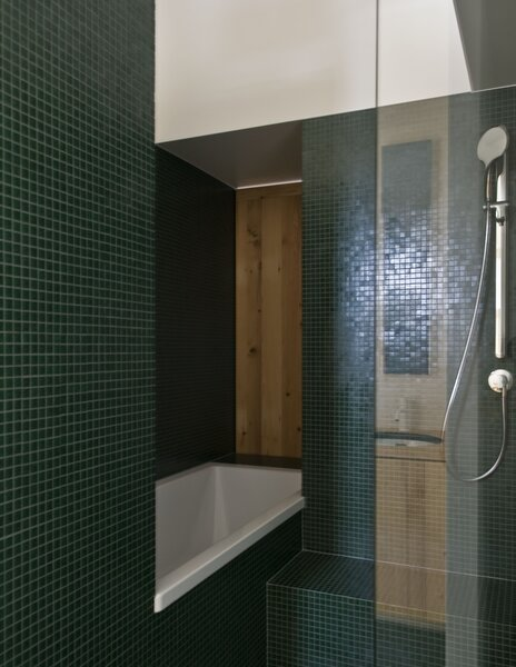 The bathroom is clad in moss-green tile, and a wooden shutter opens to a view of the living room fireplace.