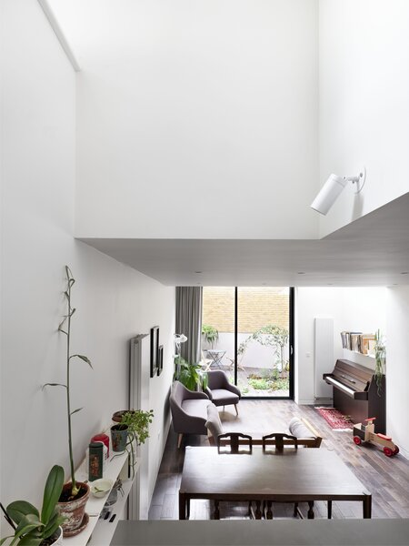 The house's east side faces a small park, increasing the amount of natural light that enters the slender building.