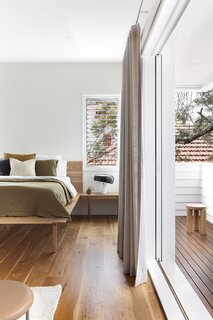 David and Hannah's new bedroom, which is located in the extension, has clean white walls, built-ins, and a large glass slider leading to a private deck.