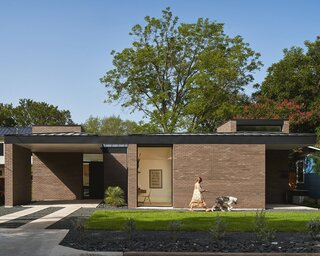 Sherry Birk and Anthony Orona, tapped HR Design Dept, whose co-principal, Eric Hughes, is a longtime friend of Anthony's, to design the midcentury-inspired, one-story house in Austin. The dark metal fascia emphasizes the home's horizontality and complements the earth-toned brick facade.