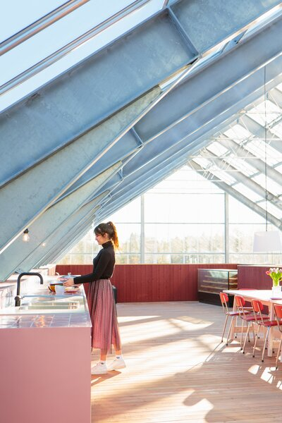 """The rooftop terrace is covered by the greenhouse roof and features a long dining table surrounded by secondhand chairs from a community center and a pink kitchen used for preparing food when entertaining. The couple hope to add cooking facilities in the future. """"It's a great place for parties,"""" says Margit. """"I haven't grown anything up here yet, but I'll start this spring."""""""