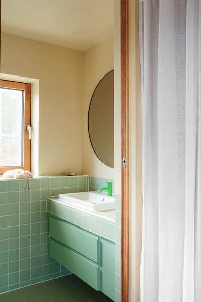 A neon green faucet pops against the softer-shaded tiles and cabinets.