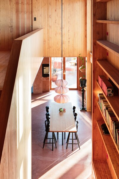 The two-story library wall that rises next to the dining area is one of the defining features of the interior. The shelves are made from glulam beams and contain storage along the base that the couple's three-year-old daughter, Velaug, uses for toys.