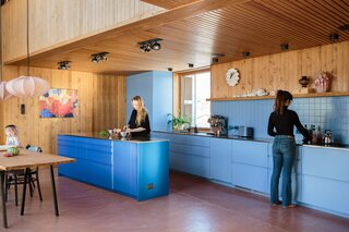 "The main kitchen, where Margit, left, is working with her niece Sarah, has a bright blue island that offers a striking contrast to the warm-toned wood and pink floors. ""We wanted a color that would transform it into an object that really stands out in the room,"" says Thurmann-Moe. ""It's almost like a sapphire."""