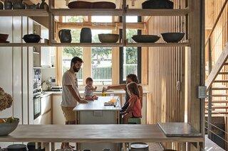 Jorge, Elvira Correa and their children gather around the kitchen island in their new home.