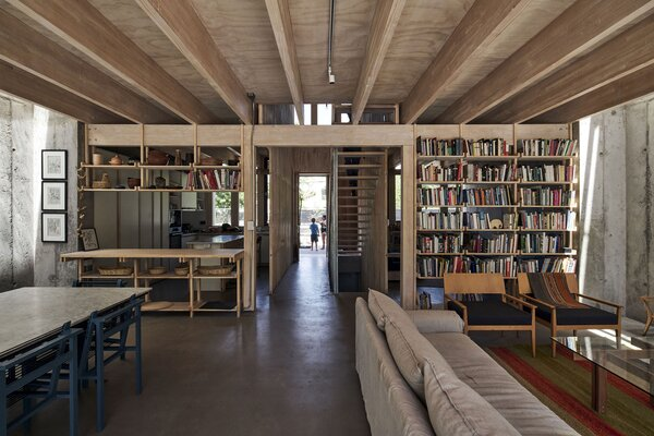 """The lattice-like bookcase separating the living room and family room is part of a design approach that Cristián says """"blurs the line between building and furniture."""" The walls and floors are concrete in all of the units."""