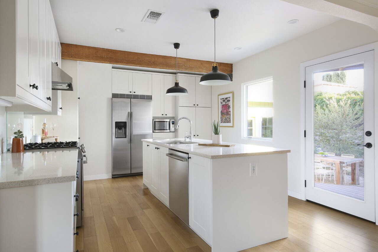 An original wooden beam spans across the width of the kitchen, a room which was treated to a complete overhaul as part of the remodel. Now, stainless steel appliances mingle with custom cabinetry while a central island provides ample space for meal prep.  Photo 6 of 15 in A Spanish-Style Charmer With a Backyard Studio Slides Onto the L.A. Market at $1.4M
