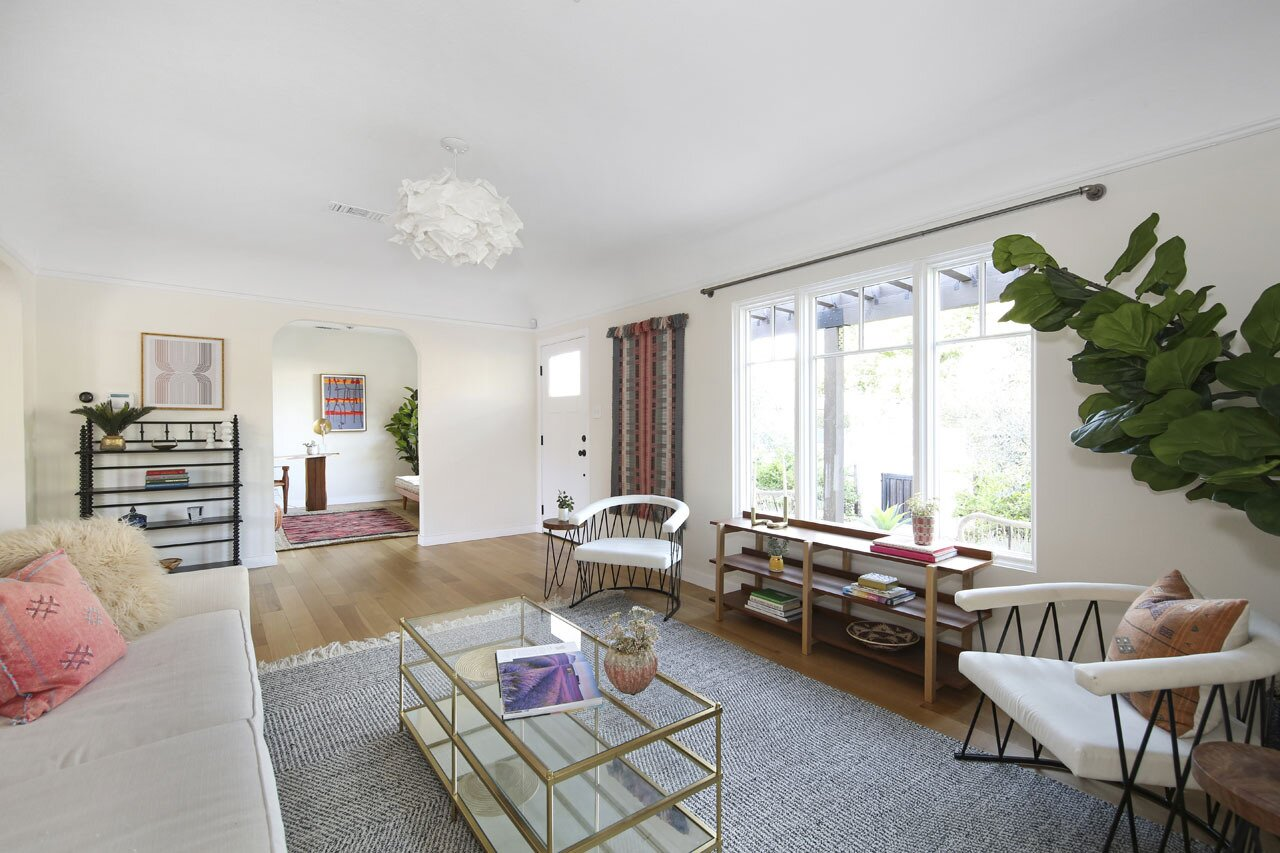The front entrance opens to the main living room. Large windows invite ample natural light inside while framing views of the landscaped yard.  Photo 3 of 15 in A Spanish-Style Charmer With a Backyard Studio Slides Onto the L.A. Market at $1.4M