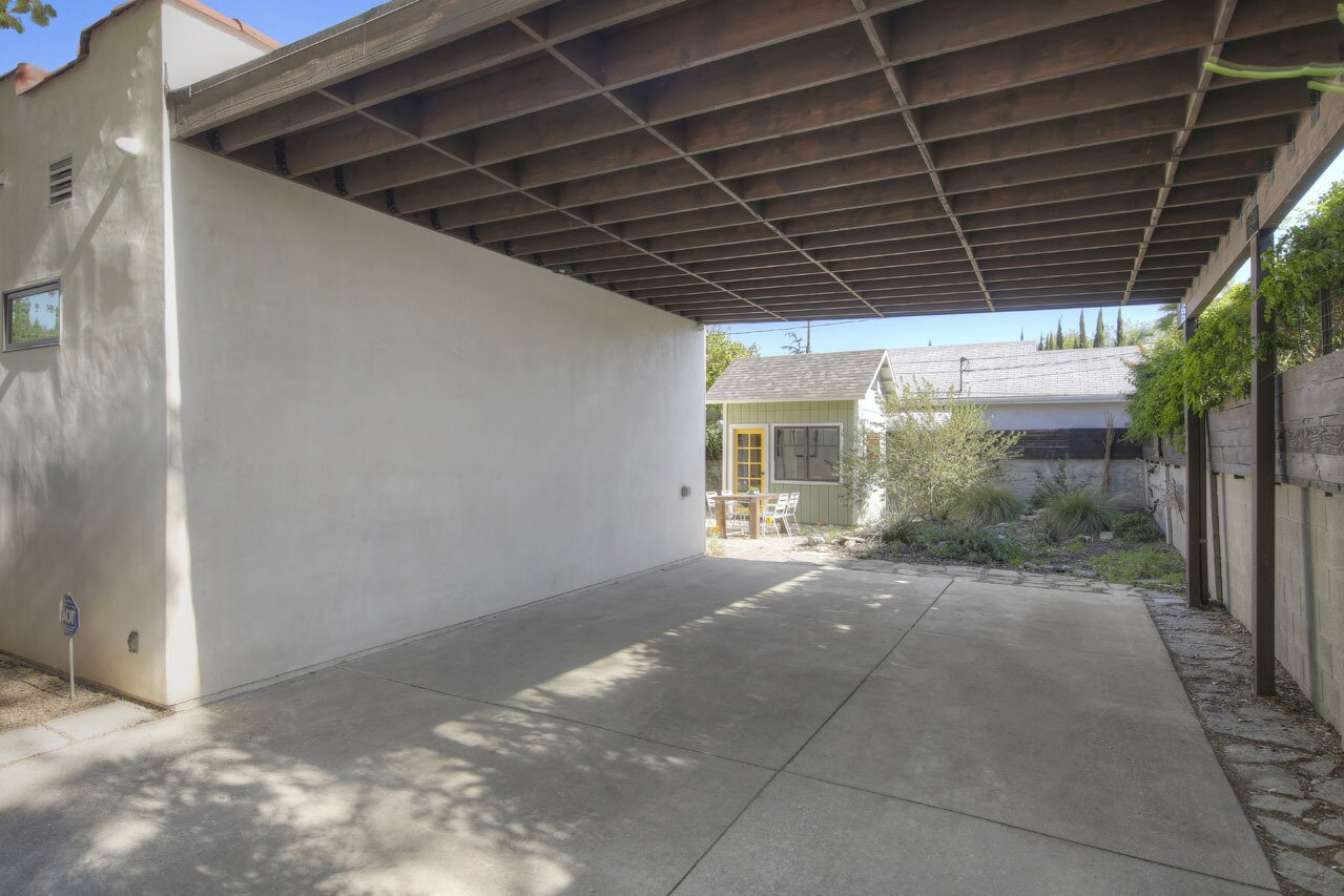 On the side of the home is a covered carport, which is accessed via an electric driveway gate.  Photo 14 of 15 in A Spanish-Style Charmer With a Backyard Studio Slides Onto the L.A. Market at $1.4M