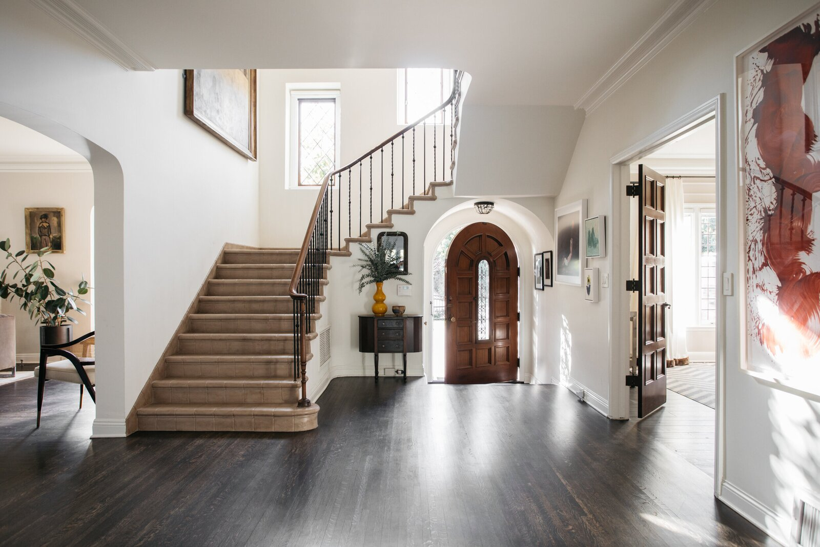 """An arched wooden door extends a warm invitation inside, opening up to the generous entryway that connects the home's primary living spaces. """"I love the wide magnesite staircase [in the foyer], and took real joy in restoring it,"""" says Lenore.  Photo 2 of 15 in A Posh Tudor-Style Home in L.A. Seeks $7M"""