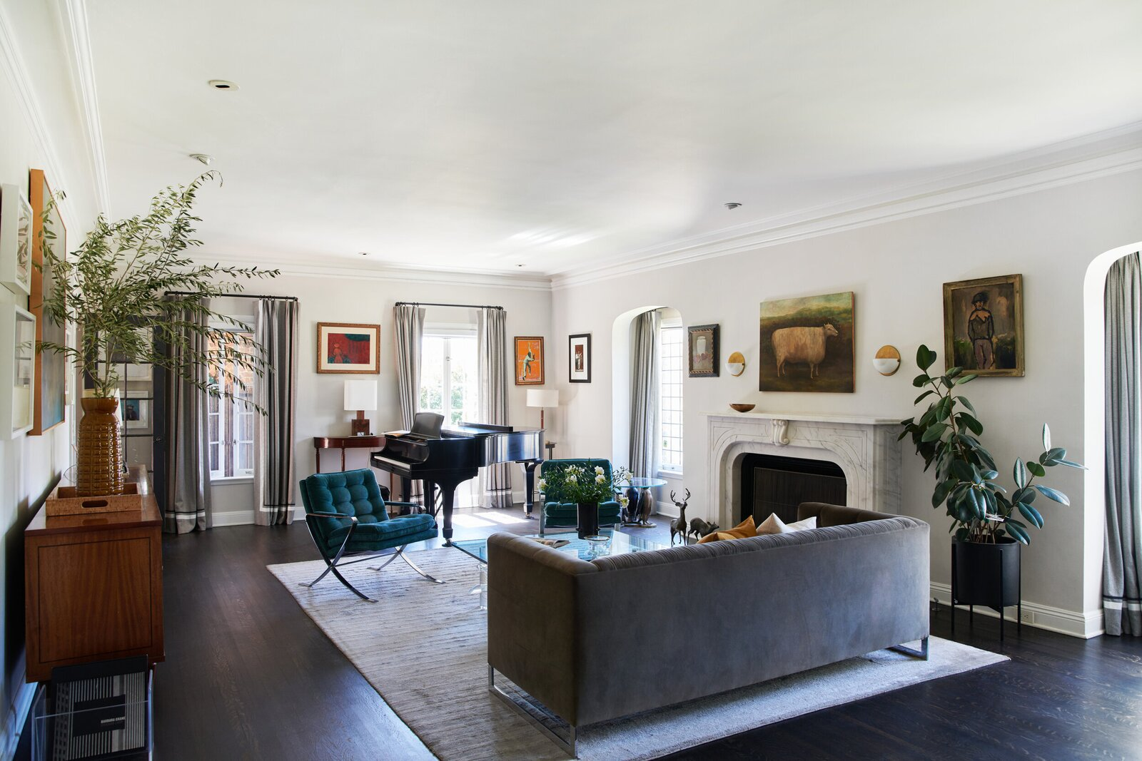 A spacious living room, complete with a marble fireplace, sits on one side of the foyer.  Photo 3 of 15 in A Posh Tudor-Style Home in L.A. Seeks $7M
