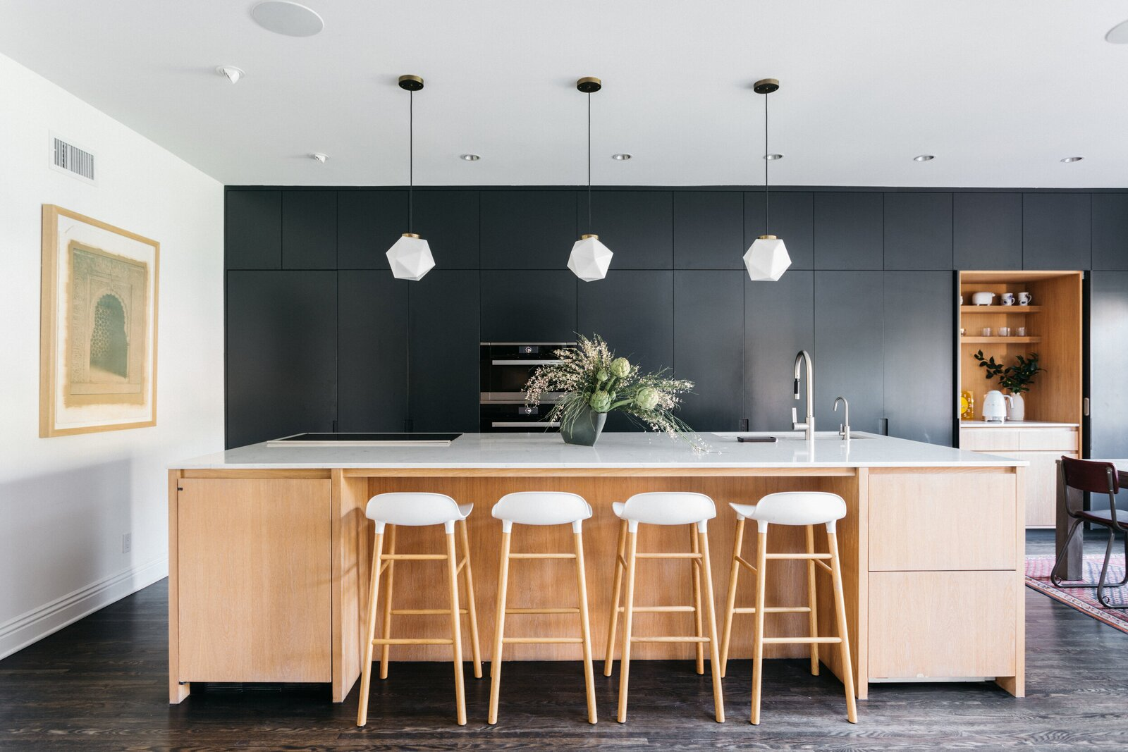 Custom black cabinetry spans the back wall in the kitchen, adding a dramatic punch of color against the geometric, white pendants hanging over the large, central island.  Photo 4 of 15 in A Posh Tudor-Style Home in L.A. Seeks $7M