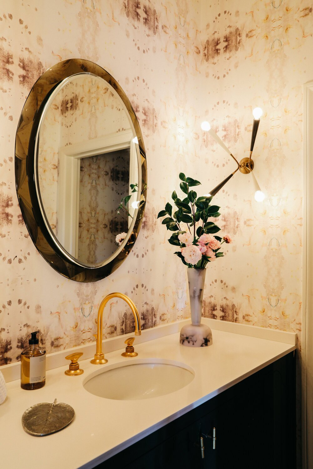 The chic half-bath on the main level is fitted with patterned wallpaper and gold accents.  Photo 8 of 15 in A Posh Tudor-Style Home in L.A. Seeks $7M