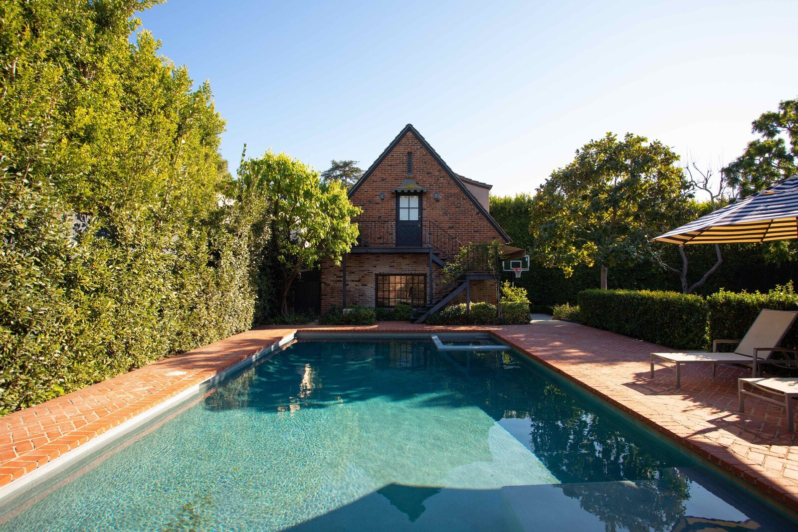 Thick vegetation surrounds the backyard, creating a tranquil city escape—idyllic for small- or large-scale entertaining. Beyond the pool is the property's two-story guesthouse.  Photo 13 of 15 in A Posh Tudor-Style Home in L.A. Seeks $7M