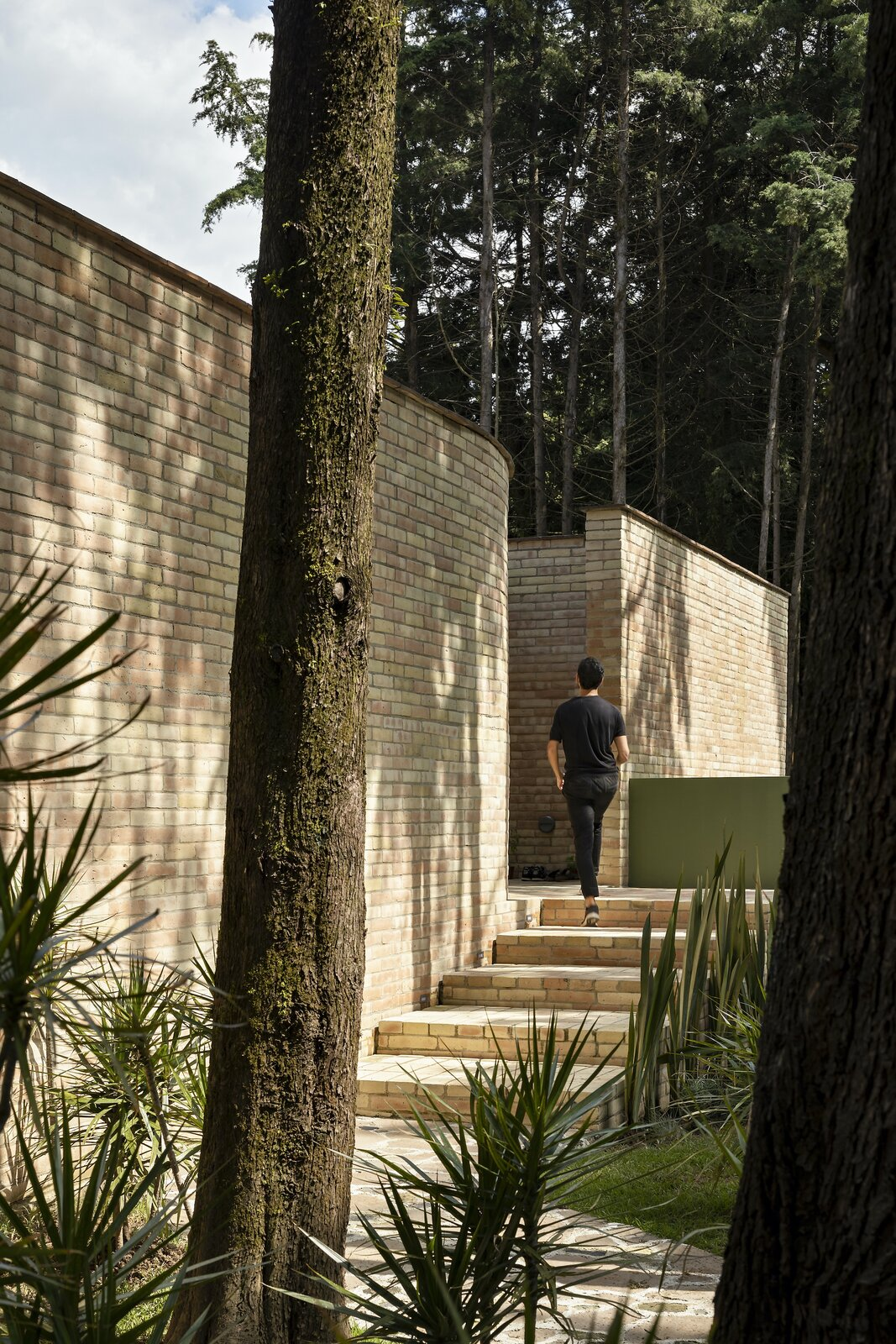 The home's imposing entrance conceals a tranquil inner courtyard.  Photo 2 of 19 in A Curvaceous Brick Home Follows the Edge of a Forest Near Mexico City