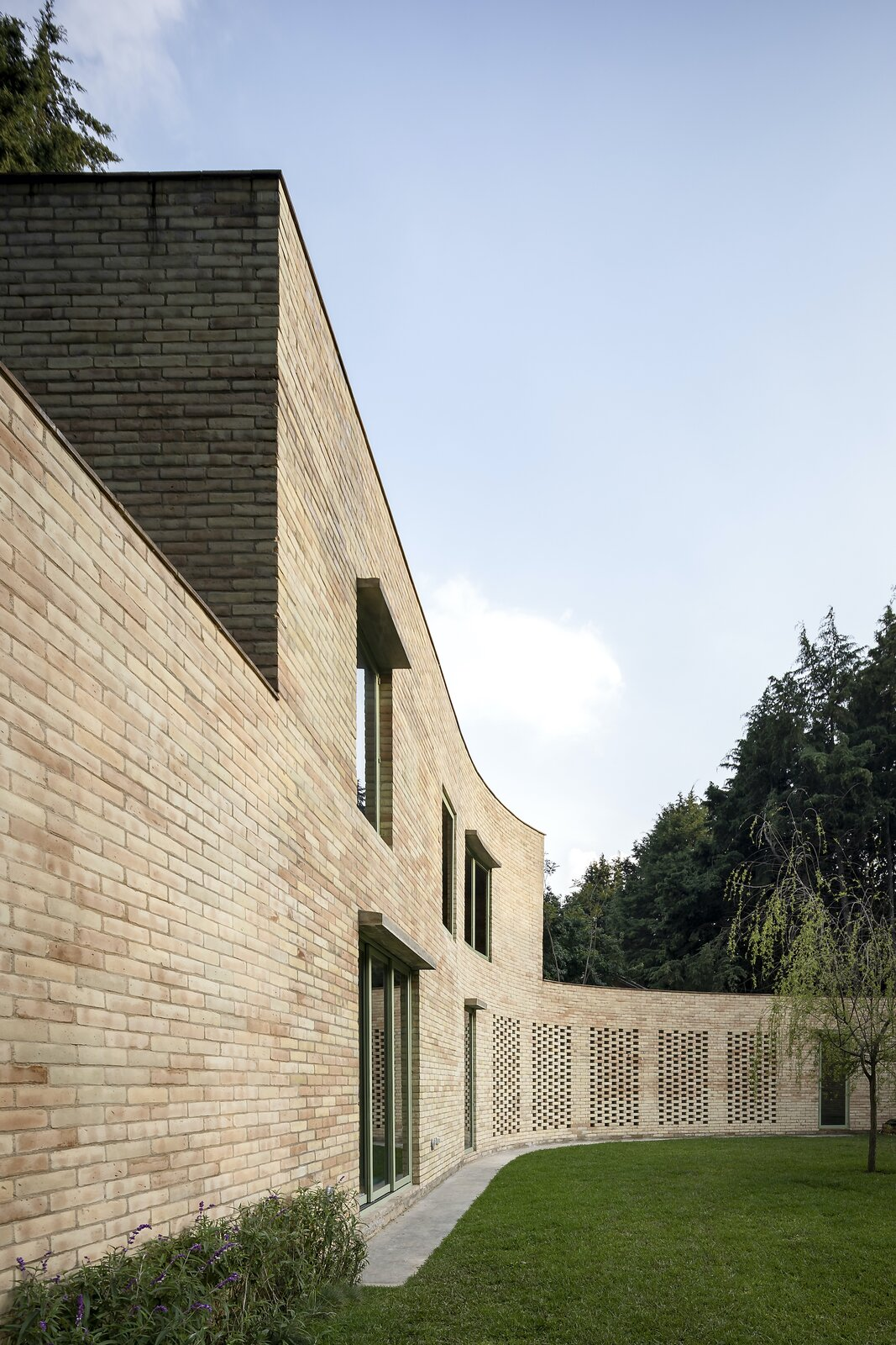 The curved brick wall was formed in relation to the pine forest on which the property is situated, and it continues throughout the main residence as an interior partition.  Photo 3 of 19 in A Curvaceous Brick Home Follows the Edge of a Forest Near Mexico City