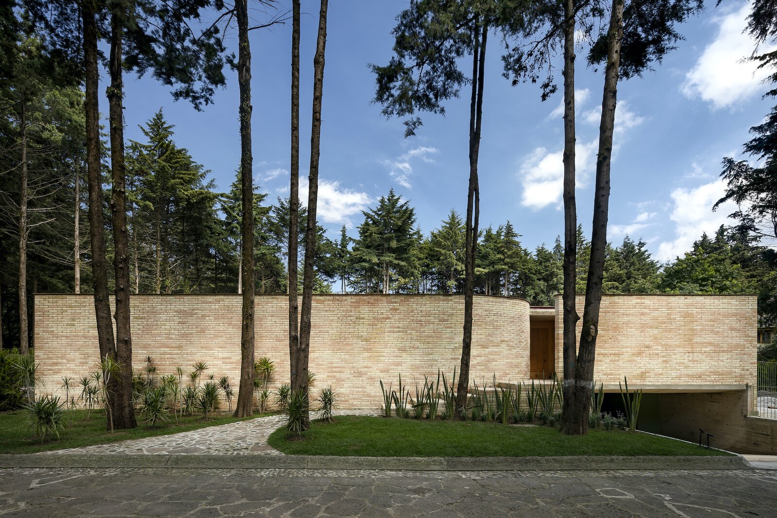 LANZA Atelier's Forest House is a triumph of artisanal expertise and sensitivity toward nature.  Photo 1 of 19 in A Curvaceous Brick Home Follows the Edge of a Forest Near Mexico City