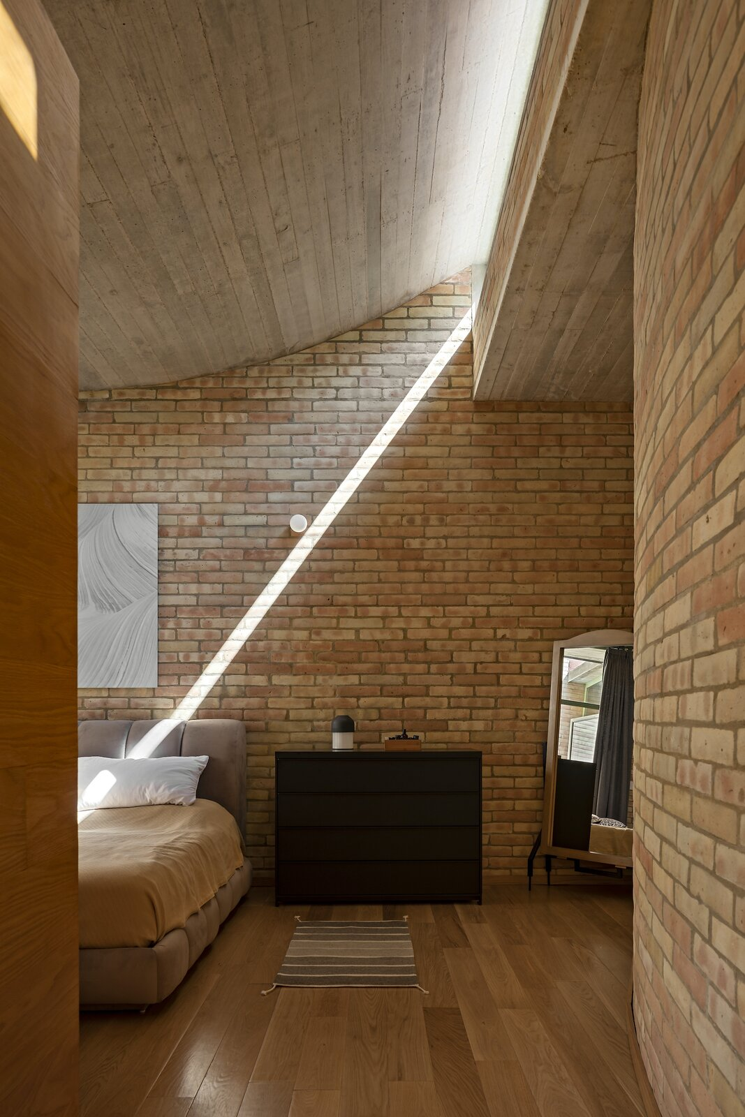 Afternoon sunshine casts a graphic beam on the wall of the master bedroom.  Photo 11 of 19 in A Curvaceous Brick Home Follows the Edge of a Forest Near Mexico City