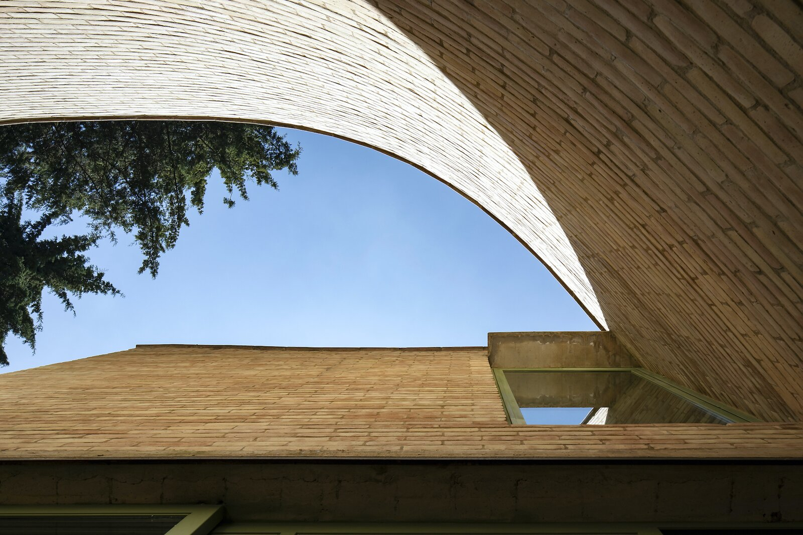 The curved form of the outer wall's edge was achieved through meticulous hand-cutting techniques to shape the bricks.  Photo 14 of 19 in A Curvaceous Brick Home Follows the Edge of a Forest Near Mexico City