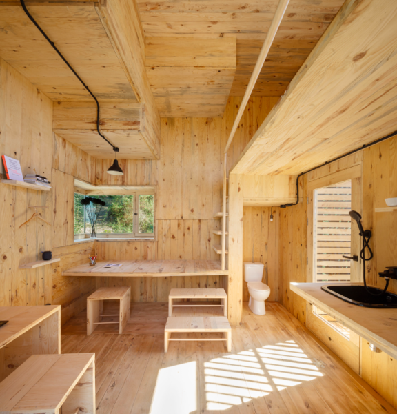 Large windows bring ample natural light inside the 130-square-foot structure. While the toilet is positioned inside the cabin, the shower is located on the exterior and is hidden from view.