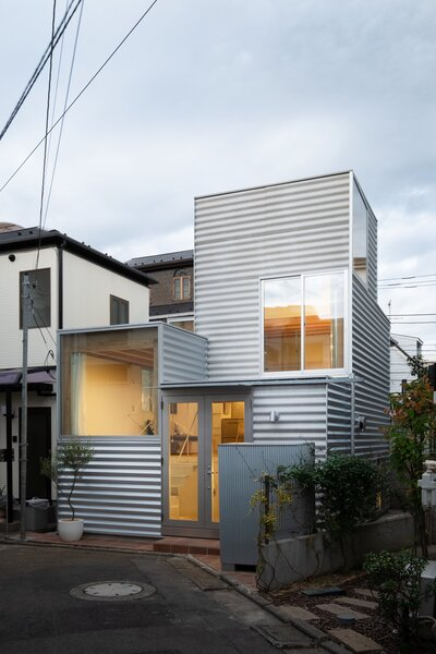 In addition to opening House Tokyo up to natural light, the large windows break up the corrugated metal facade.