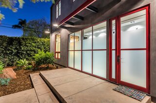 A bright shade of red framing the door and windows pops against the home's dark gray facade.