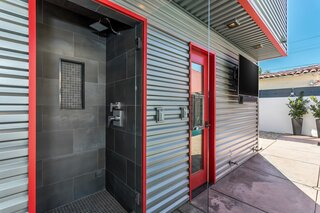 Steps from the pool, a tiled outdoor shower sits next to the entrance of the attached ADU.