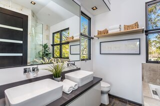 Each of the four and a half bathrooms located in the main house is dressed in designer finishes. In addition to a double vanity, the primary bath also presents an oversize glass shower.