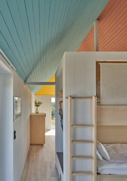 The cabin can comfortably accommodate four adults. A set of bunk beds are positioned on one side of a wall that separates the living room and sleeping quarters.