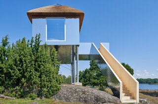 The mirrored villa rests on 43-foot-high pillars and is accessed via a long wooden staircase.