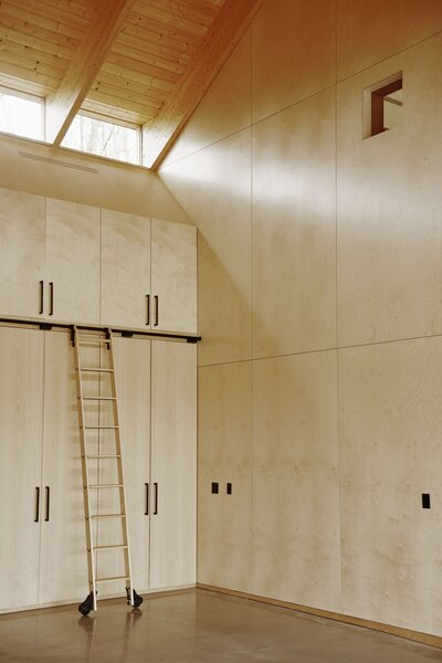 An eight-foot sliding ladder provides access to upper cabinets in the garage of a carriage house in Northwestern Connecticut designed by architect Aya Maceda for Rakesh and Amanda Wilson.
