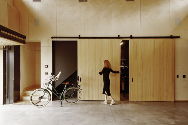 On a side wall, sleek barn doors open to reveal a storage area for bikes. Stairs near the garage entrance, which features a door from Renlita, lead to a vaulted loft that was originally intended as an exercise room but is now used by Rakesh as an office.