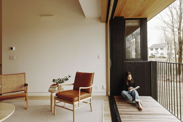 The folding glass door extending the living space with a wood-lined deck is from Marvin.