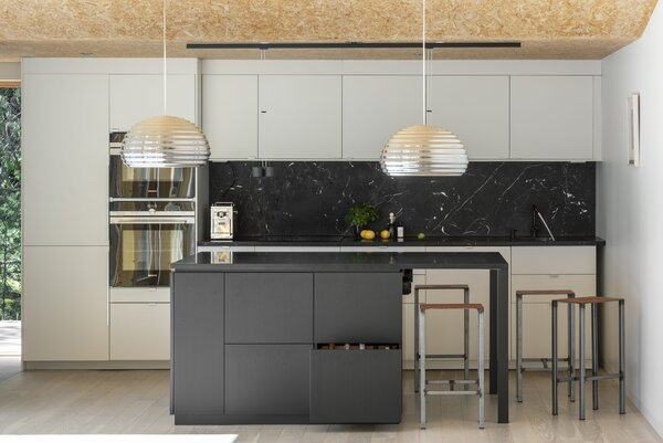A pair of Splügen Braü pendants from Flos hang near a kitchen island topped with black Swedish granite. The faucets are from Vola and the appliances are from Siemens.
