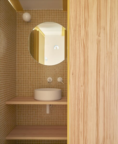 Yellow tiles add a fun pop of color in the bathroom.