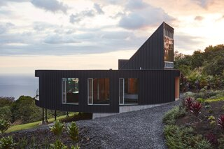 """With a circular plan capped by a finlike flourish, a 2,400-square-foot home designed by Craig Steely for a Hawaii farm has a striking profile, but its construction is based on traditional pole houses raised on tall piloti. """"Part of the reason for building a pole house was that it would sort of hover above the farm and toward the view,"""" says Steely."""