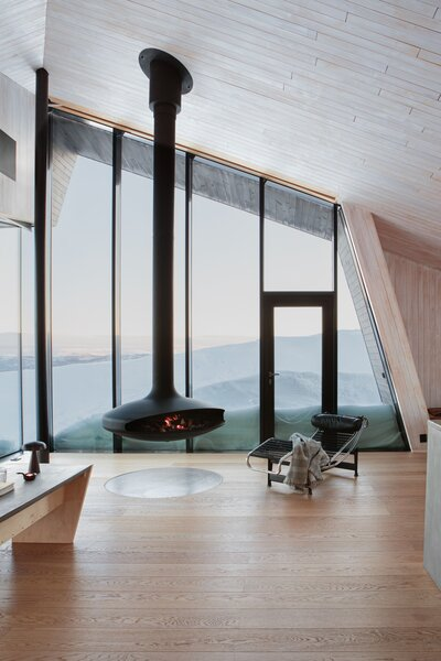 In the living area, floor-to-ceiling windows by Schüco frame a Gyrofocus suspended rotating fireplace by Focus. At night, a crackling fire appears to hover in the dark.