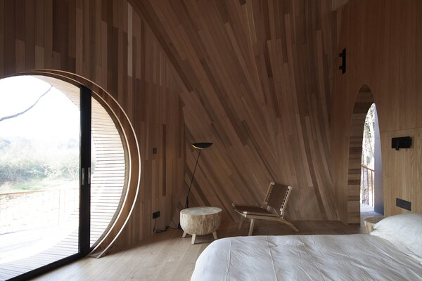 An external staircase provides access to the cabin's interior, which boasts a similar wood-clad aesthetic.