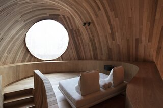 The upper-level lounge features an oculus window that overlooks the forested landscape.
